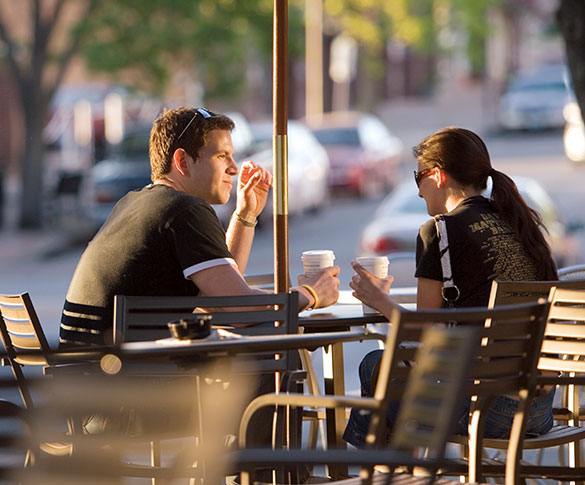 Man and woman drinking coffee at cafe table on downtown sidewalk