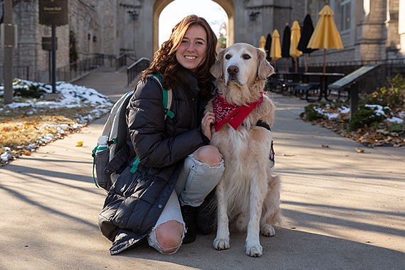 Student poses with service dog in front of Memorial Union