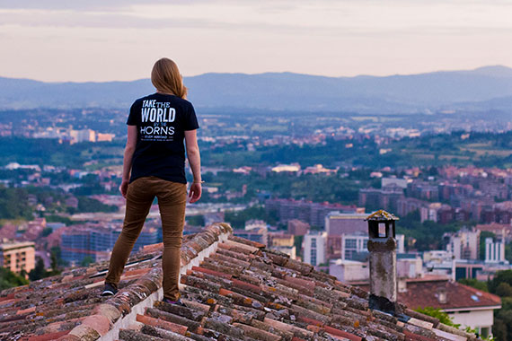 "Student wearing t-shirt that reads ""Take the world by the horns. Study abroad"" standing on rooftop looking out over village"