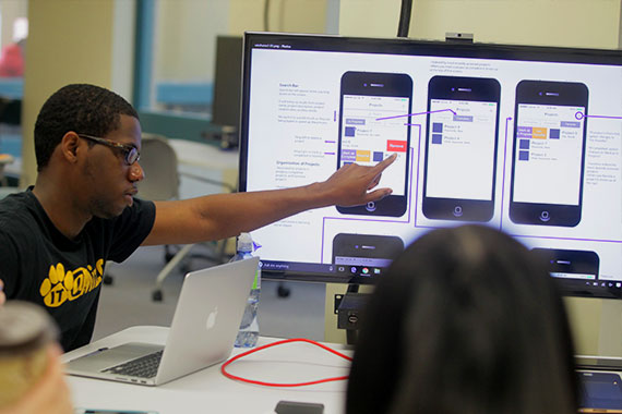 Student pointing to mobile phone app mock-ups on screen