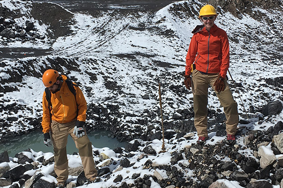 A team of graduate students stand on snowy rocks while field testing the lava suits