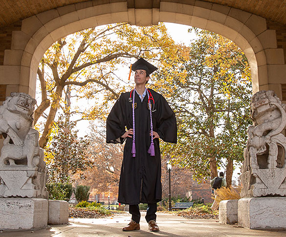 Student wearing cap and gown standing between lion statues under journalism archway