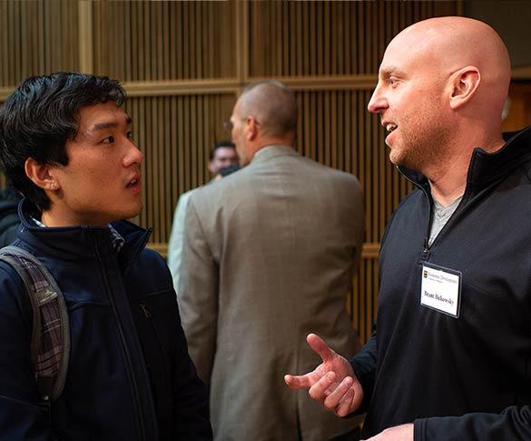 Two men discuss entrepreneurship during networking event