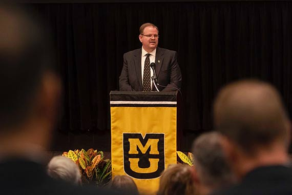 Chancellor Cartwright stands at podium to give annual state of the university address