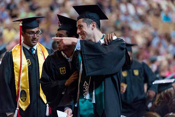 Three men in cap and gown smile during commencement ceremony