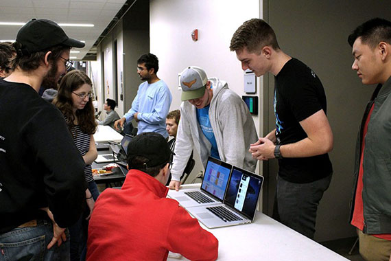 Tiger Hacks participants huddled around a computer during contest