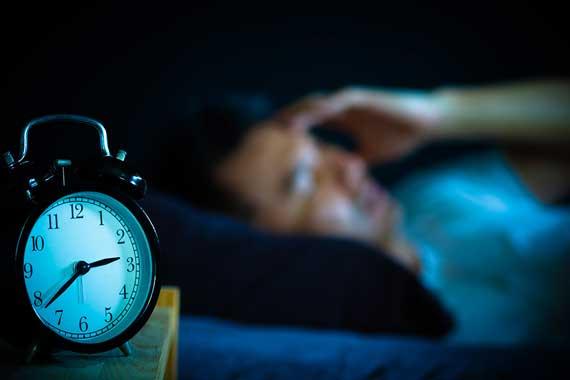 Alarm clock and man trying to sleep