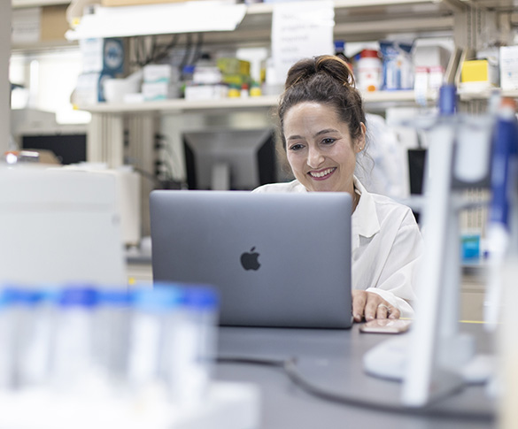 Faculty member working on laptop in research lab